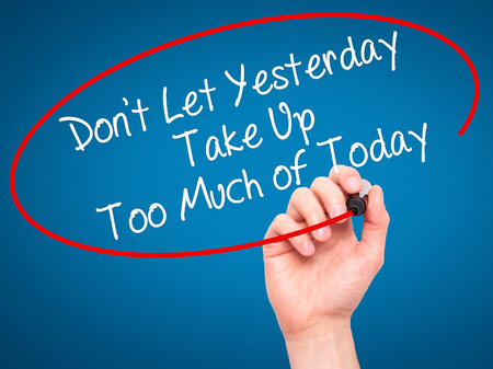 street wise: Man Hand writing Dont Let Yesterday Take Up Too Much of Today with black marker on visual screen. Isolated on background. Business, technology, internet concept. Stock Photo Stock Photo