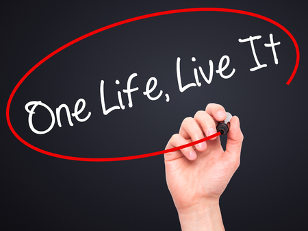 adrenaline rush: Man Hand writing One Life Live It with black marker on visual screen. Isolated on background. Business, technology, internet concept. Stock Photo