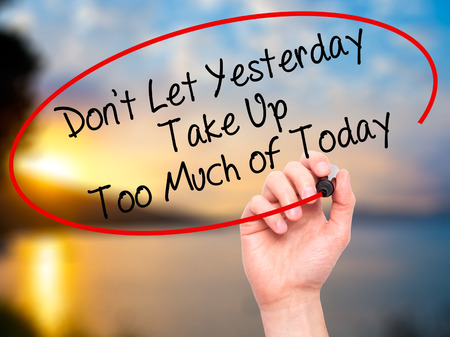 yesterday: Man Hand writing Dont Let Yesterday Take Up Too Much of Today with black marker on visual screen. Isolated on background. Business, technology, internet concept. Stock Photo Stock Photo