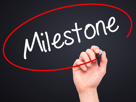 milestone: Man Hand writing Milestone with black marker on visual screen. Isolated on background. Business, technology, internet concept. Stock Photo