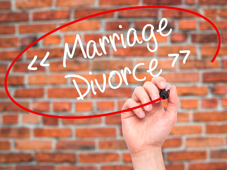 severance: Man Hand writing Marriage - Divorce with black marker on visual screen. Isolated on background. Business, technology, internet concept. Stock Photo