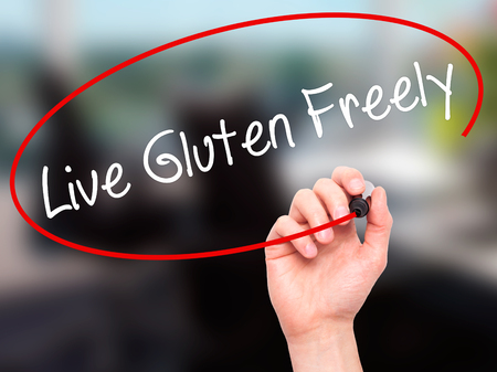 nota: Man Hand writing Live Gluten Freely with black marker on visual screen. Isolated on background. Business, technology, internet concept. Stock Photo