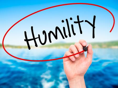 humildad: Hombre de la mano escribiendo Humildad con marcador negro en la pantalla visual. Aislado en el fondo. Negocios, la tecnolog�a, el concepto de internet. Foto de stock Foto de archivo