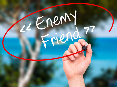 untrustworthy: Man Hand writing Enemy - Friend with black marker on visual screen. Isolated on background. Business, technology, internet concept. Stock Photo