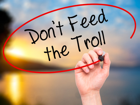 ludicrous: Man Hand writing Dont Feed the Troll with black marker on visual screen. Isolated on background. Business, technology, internet concept. Stock Photo