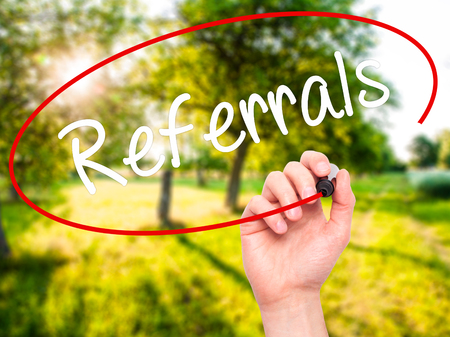 referidos: Man Hand writing Referrals with black marker on visual screen. Isolated on background. Business, technology, internet concept. Stock Photo