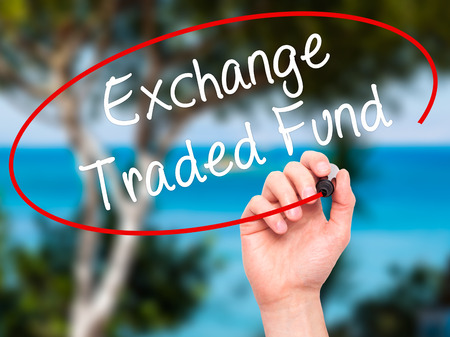 traded: Man Hand writing Exchange Traded Fund with black marker on visual screen. Isolated on background. Business, technology, internet concept. Stock Photo Stock Photo