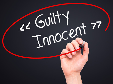 fair trial: Man Hand writing Guilty - Innocent with black marker on visual screen. Isolated on background. Business, technology, internet concept. Stock Photo