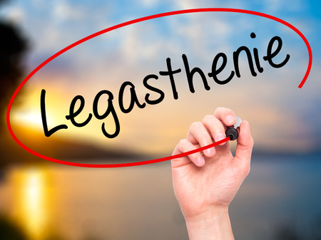 dyslexic: Man Hand writing Legasthenie (Dyslexia in German) with black marker on visual screen. Isolated on background. Business, technology, internet concept. Stock Photo