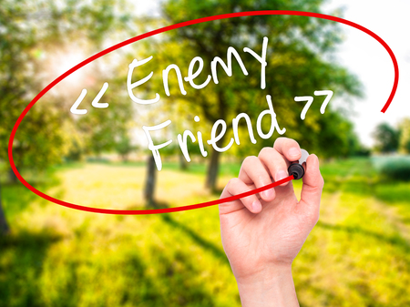 pretender: Man Hand writing Enemy - Friend with black marker on visual screen. Isolated on background. Business, technology, internet concept. Stock Photo