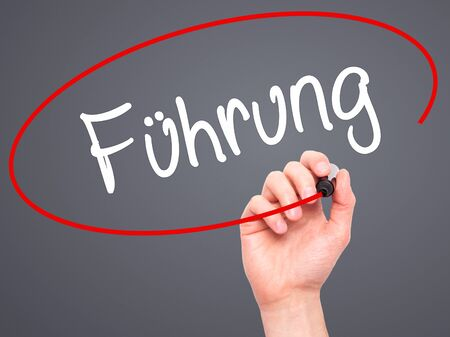 fulfill: Man Hand writing Fuhrung (Leadership in German) with black marker on visual screen. Isolated on background. Business, technology, internet concept. Stock Photo