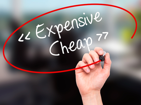 Man Hand writing Expensive - Cheap with black marker on visual screen. Isolated on background. Business, technology, internet concept. Stock Photo Stock Photo