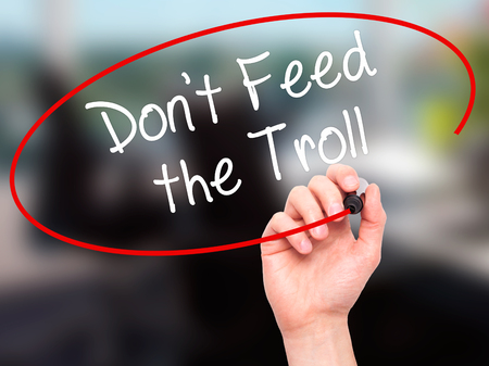 trolling: Man Hand writing Dont Feed the Troll with black marker on visual screen. Isolated on background. Business, technology, internet concept. Stock Photo