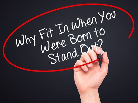 adentro y afuera: Man Hand writing Why Fit In When You Were Born to Stand Out? with black marker on visual screen. Isolated on background. Business, technology, internet concept. Stock Photo