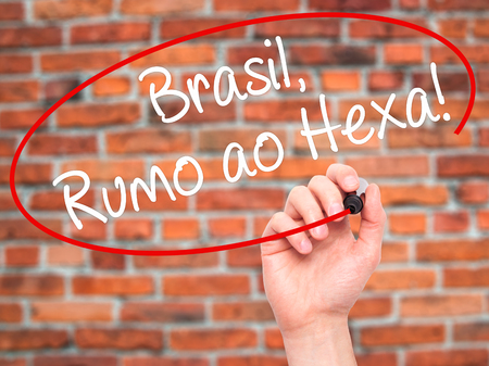 ao: Man Hand writing Brasil, Rumo ao Hexa! with black marker on visual screen. Isolated on background. Business, technology, internet concept. Stock Photo