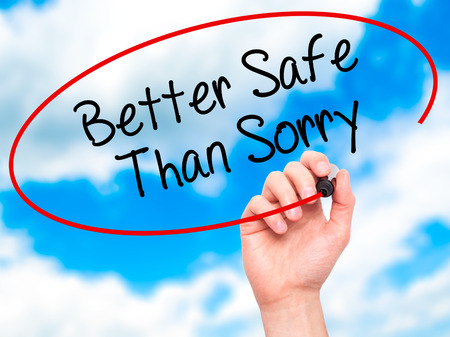 safety first: Man Hand writing Better Safe Than Sorry with black marker on visual screen. Isolated on background. Business, technology, internet concept. Stock Photo