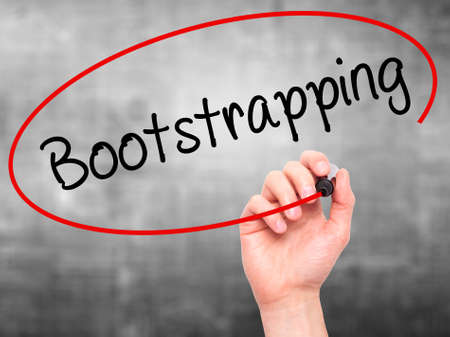 bootstrap: Man Hand writing Bootstrapping with black marker on visual screen. Isolated on background. Business, technology, internet concept. Stock Photo Stock Photo