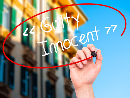 presumption: Man Hand writing Guilty - Innocent with black marker on visual screen. Isolated on background. Business, technology, internet concept. Stock Photo