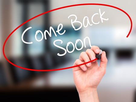 will return: Man Hand writing Come Back Soon with black marker on visual screen. Isolated on background. Business, technology, internet concept. Stock Photo Stock Photo
