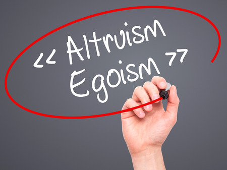 altruism: Man Hand writing Altruism - Egoism with black marker on visual screen. Isolated on background. Business, technology, internet concept. Stock Photo
