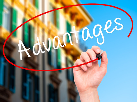 advantages: Man Hand writing Advantages with black marker on visual screen. Isolated on background. Business, technology, internet concept. Stock Photo Stock Photo