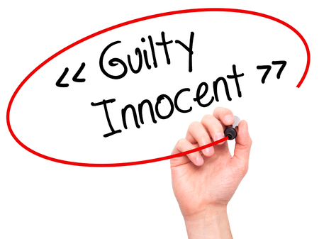 innocent: Man Hand writing Guilty - Innocent with black marker on visual screen. Isolated on background. Business, technology, internet concept. Stock Photo
