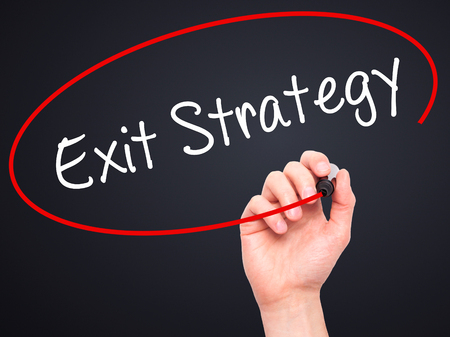 downsize: Man Hand writing Exit Strategy with black marker on visual screen. Isolated on background. Business, technology, internet concept. Stock Photo