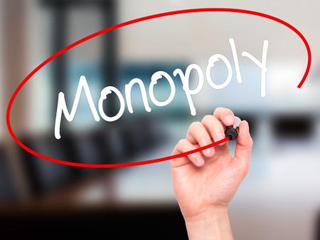monopolio: Hombre de la mano escribiendo Monopoly con marcador negro en la pantalla visual. Aislado en el fondo. Negocios, la tecnolog�a, el concepto de internet. Foto de stock