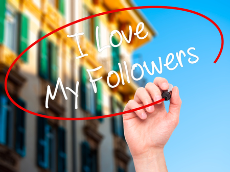 free me: Man Hand writing I Love My Followers with black marker on visual screen. Isolated on background. Business, technology, internet concept. Stock Photo
