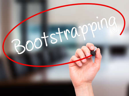Man Hand writing Bootstrapping with black marker on visual screen. Isolated on background. Business, technology, internet concept. Stock Photo Stock Photo