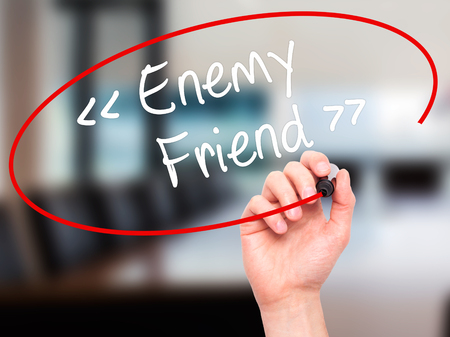 Man Hand writing Enemy - Friend with black marker on visual screen. Isolated on background. Business, technology, internet concept. Stock Photo