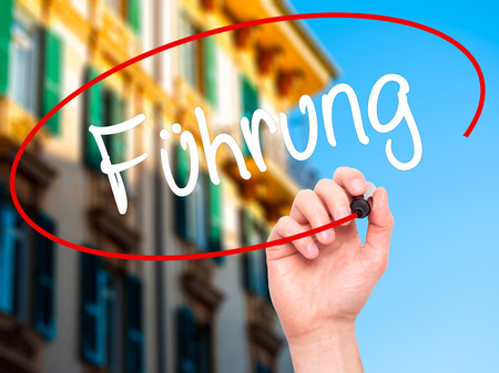powerful creativity: Man Hand writing Fuhrung (Leadership in German) with black marker on visual screen. Isolated on background. Business, technology, internet concept. Stock Photo