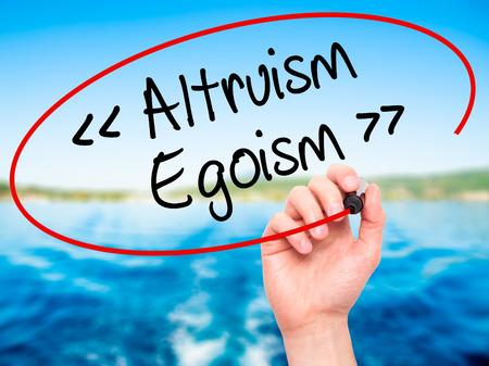 altruismo: Hombre de la mano de escritura Altruismo - Ego�smo con marcador negro en la pantalla visual. Aislado en el fondo. Negocios, la tecnolog�a, el concepto de internet. Foto de stock