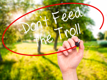 sarcastic: Man Hand writing Dont Feed the Troll with black marker on visual screen. Isolated on background. Business, technology, internet concept. Stock Photo