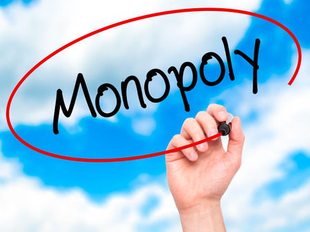 Man Hand writing Monopoly with black marker on visual screen. Isolated on background. Business, technology, internet concept. Stock Photo
