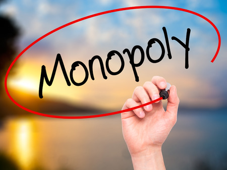 escrow: Man Hand writing Monopoly with black marker on visual screen. Isolated on background. Business, technology, internet concept. Stock Photo