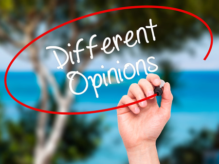 differing: Man Hand writing Different Opinions with black marker on visual screen. Isolated on background. Business, technology, internet concept. Stock Photo