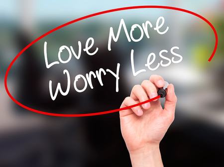 in need of space: Man Hand writing Love More Worry Less with black marker on visual screen. Isolated on background. Business, technology, internet concept. Stock Photo