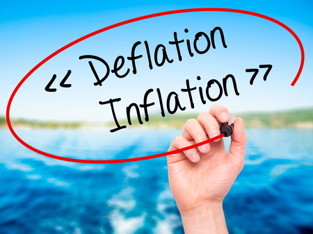 Man Hand writing Deflation - Inflation with black marker on visual screen. Isolated on background. Business, technology, internet concept. Stock Photo
