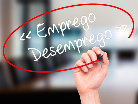 need direction: Man Hand writing Emprego Desemprego (Employment - Unemployment in Portuguese)  with black marker on visual screen. Isolated on background. Business, technology, internet concept. Stock Photo