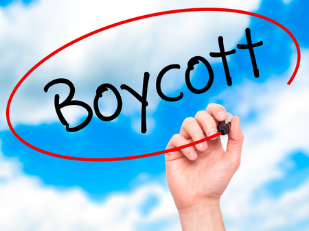consumer rights: Man Hand writing Boycott with black marker on visual screen. Isolated on background. Business, technology, internet concept. Stock Photo Stock Photo