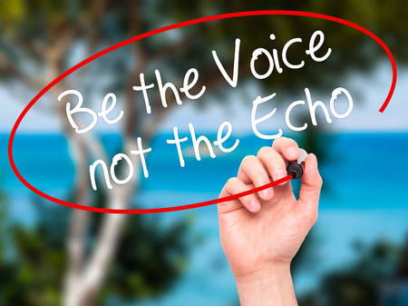 to be or not to be: Man Hand writing Be the Voice not the Echo with black marker on visual screen. Isolated on background. Business, technology, internet concept. Stock Photo