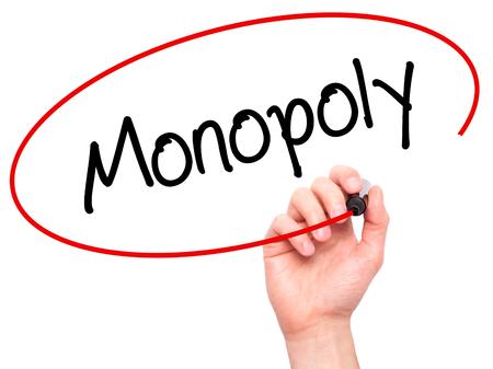 monopoly: Hombre de la mano escribiendo Monopoly con marcador negro en la pantalla visual. Aislado en el fondo. Negocios, la tecnología, el concepto de internet. Foto de stock