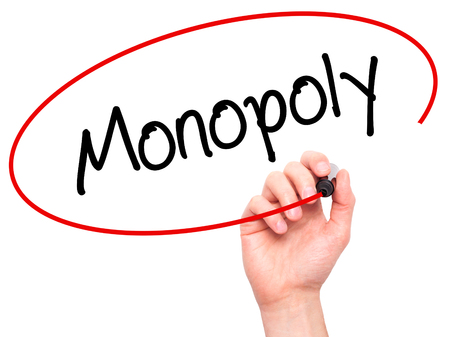 monopolio: Man Hand writing Monopoly with black marker on visual screen. Isolated on background. Business, technology, internet concept. Stock Photo