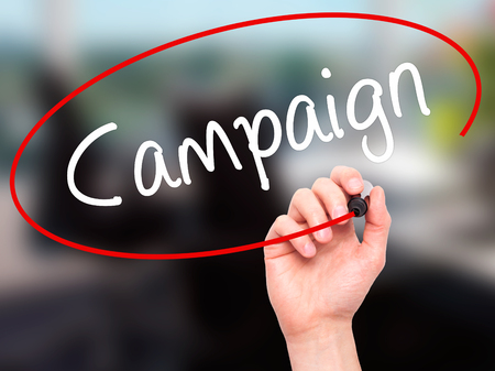 Man Hand writing Campaign with black marker on visual screen. Isolated on background. Business, technology, internet concept. Stock Photo