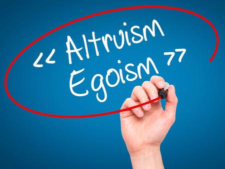 altruism: Hombre de la mano de escritura Altruismo - Egoísmo con marcador negro en la pantalla visual. Aislado en el fondo. Negocios, la tecnología, el concepto de internet. Foto de stock