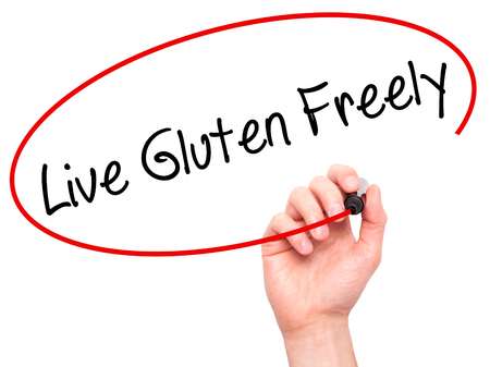 freely: Man Hand writing Live Gluten Freely with black marker on visual screen. Isolated on background. Business, technology, internet concept. Stock Photo