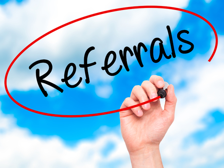 referrals: Man Hand writing Referrals with black marker on visual screen. Isolated on background. Business, technology, internet concept. Stock Photo