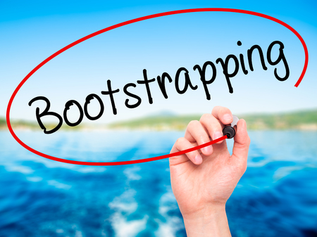 funded: Man Hand writing Bootstrapping with black marker on visual screen. Isolated on background. Business, technology, internet concept. Stock Photo Stock Photo