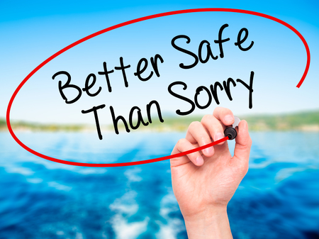 better safe than sorry: Man Hand writing Better Safe Than Sorry with black marker on visual screen. Isolated on background. Business, technology, internet concept. Stock Photo